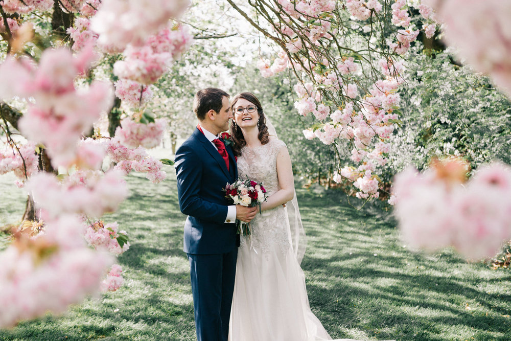 The newly married couple is posing joyfully under the cherry blossoms in Beaconsfield, UK.