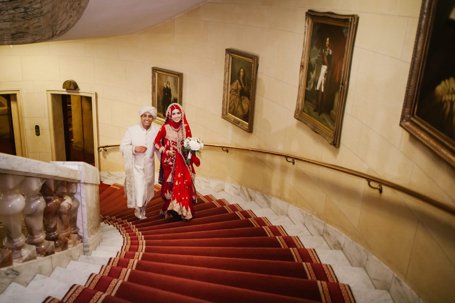 The married couple is smiling while walking upstairs at the Royal Horseguards Hotel.
