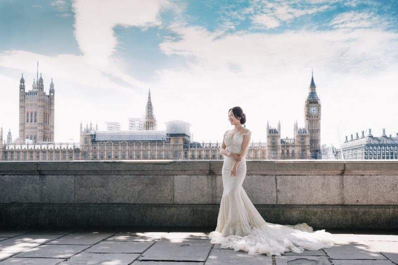 The bride is happily posing during the wedding day photo shoot near the London Clock Tower
