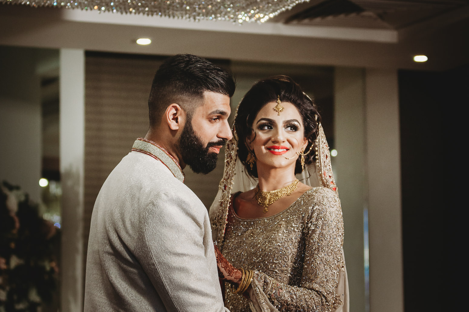 The new married couple is smiling and posing for their wedding photo shoot at the Royal Nawaab Hotel in London.