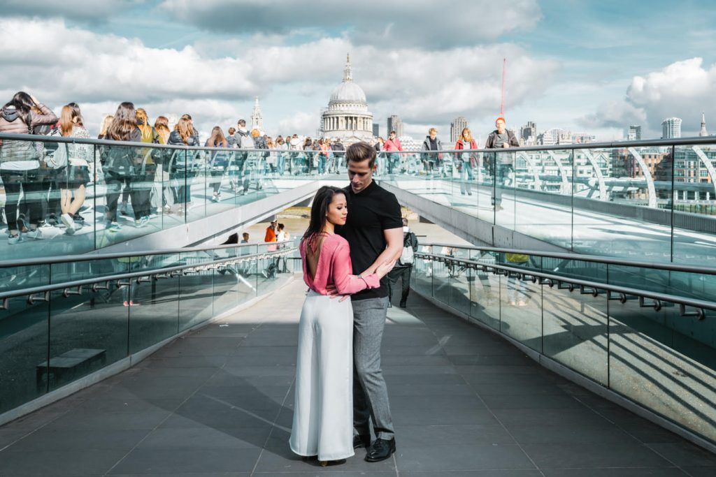 A new engaged couple is posing for their engagement photo shoot at the millennium bridge.
