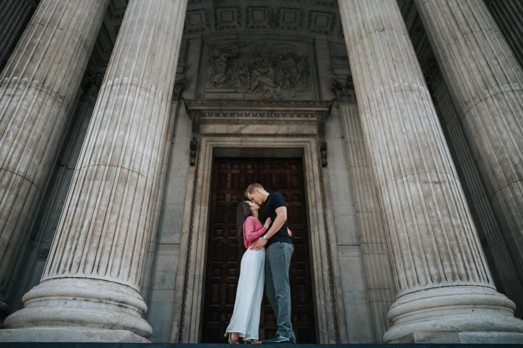 A sweet couple on their engagement photo shoot is kissing each other between two big pillars.