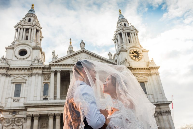 The newlywed is under the bride's veil during their photo shoot in front of St. Paul's Cathedral.