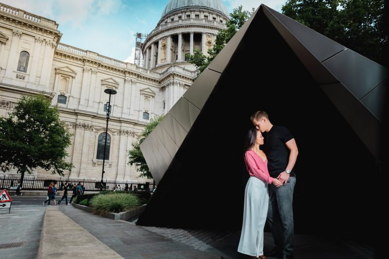A groom to be is kissing the forehead of his future wife during their pre-wedding photoshoot near St. Paul's Cathedral.