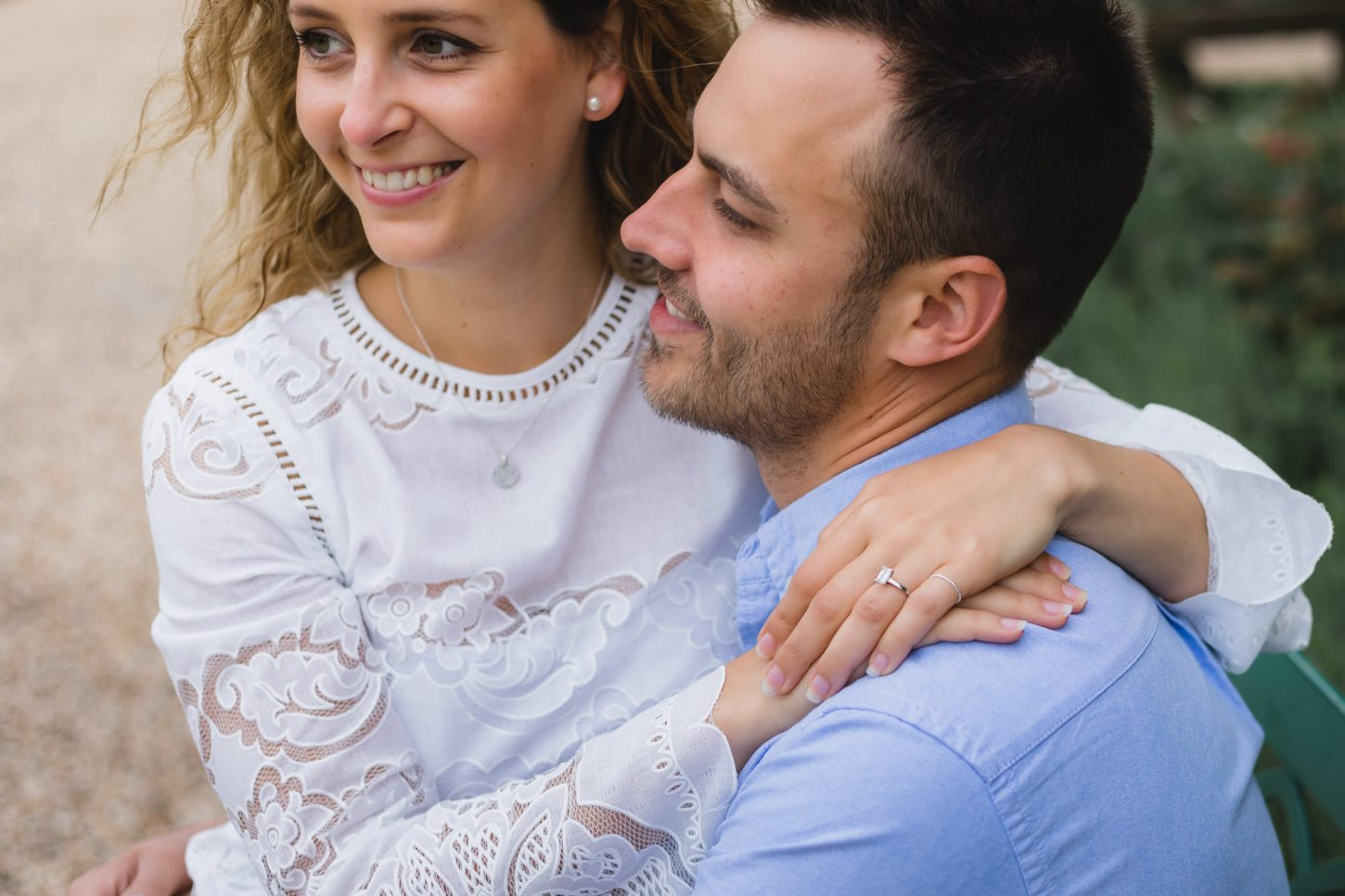 A romantic couple on their engagement photo shoot is posing and hugging each other.