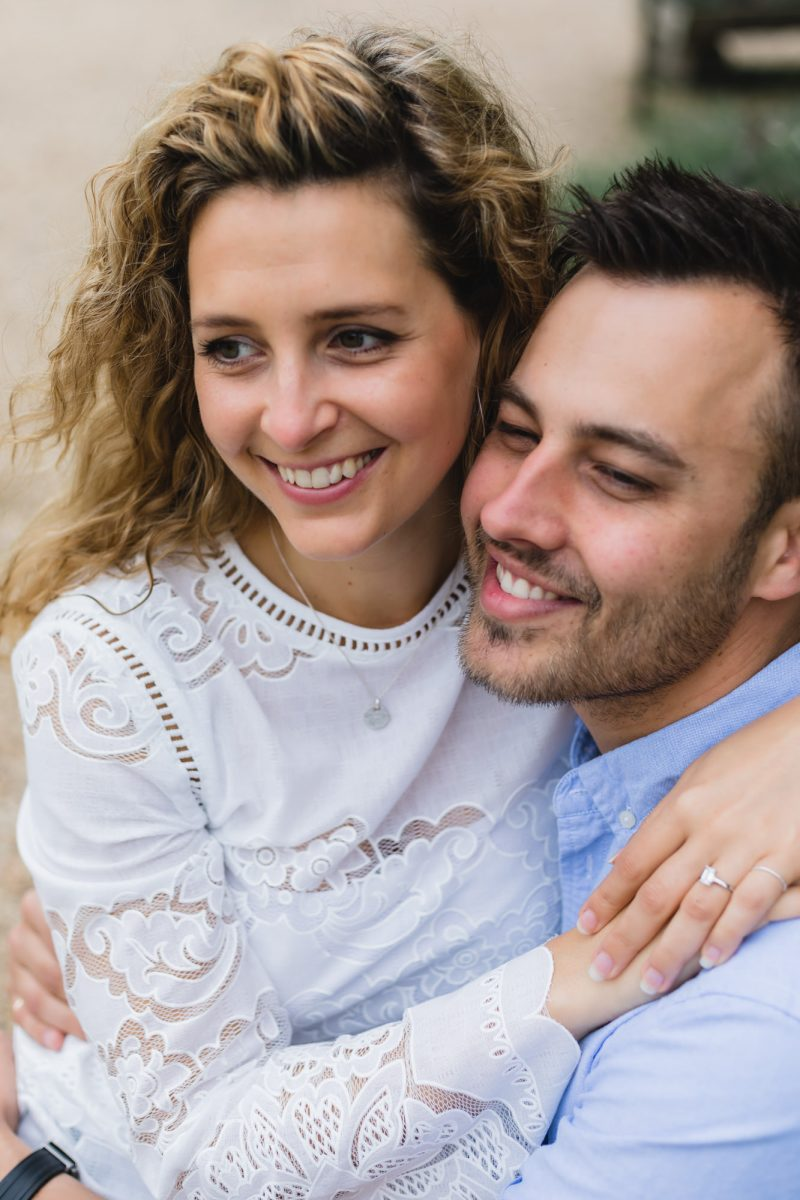 The new couple on their engagement photo shoot is posing and hugging each other.