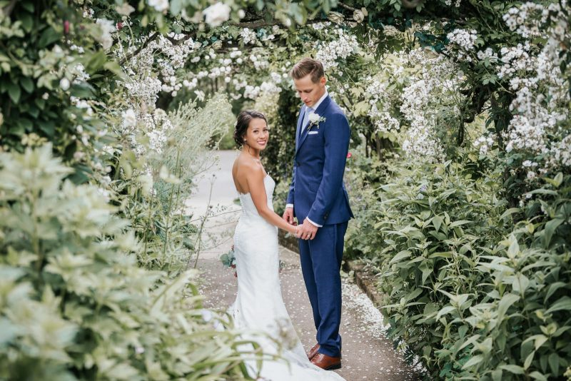 The couple is walking happily on their natural outdoor wedding engagement photo shoot in London UK.