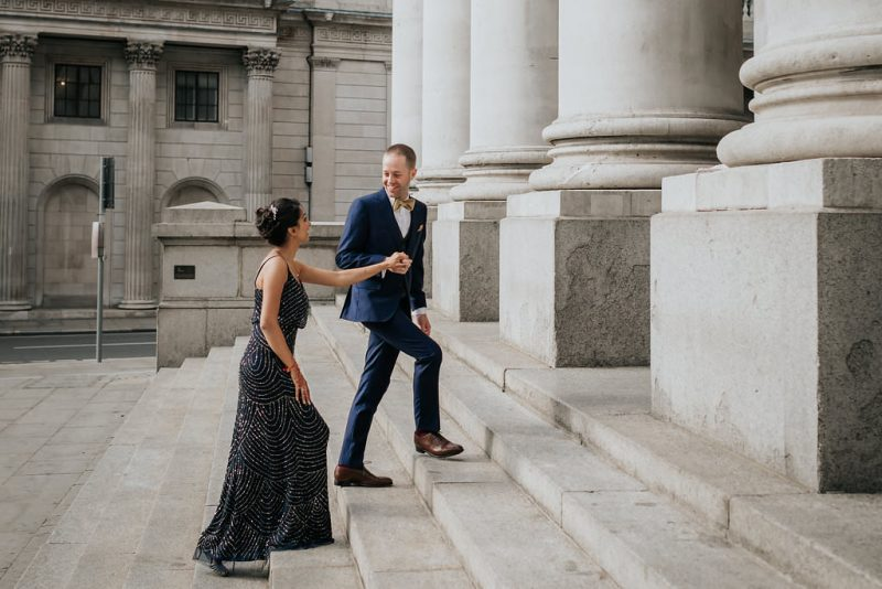 The newly engaged couple staring at each other is smiling while walking upstairs at the Banking Hall, London.