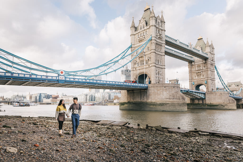A new couple is walking together under the London Bridge during their pre-wedding photoshoot.