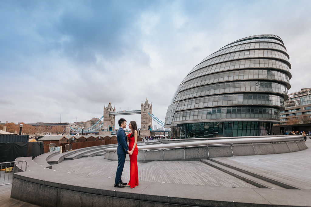A lovely couple is staring merrily at each other while holding hands near the Tower Bridge.