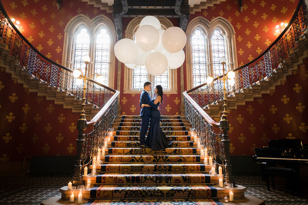 Sweet couple standing on the stairs is holding big balloons at the St. Pancras Renaissance Hotel.