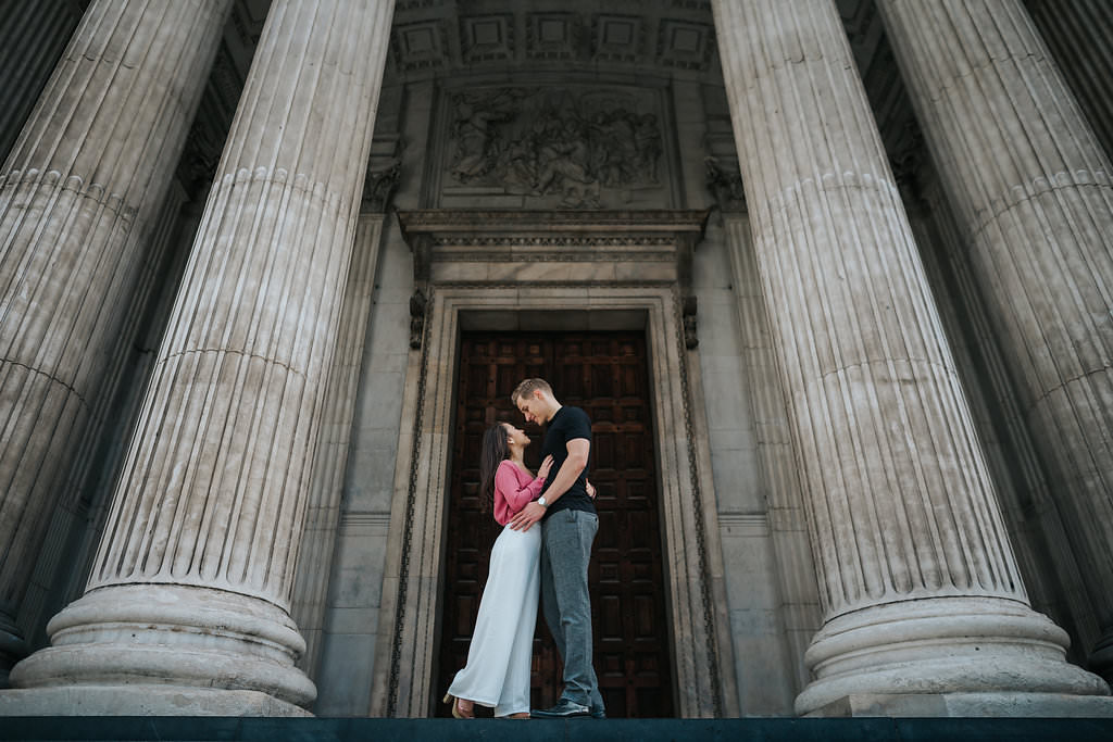 The couple is posing and staring at each other between two big pillars during their photo shoot.