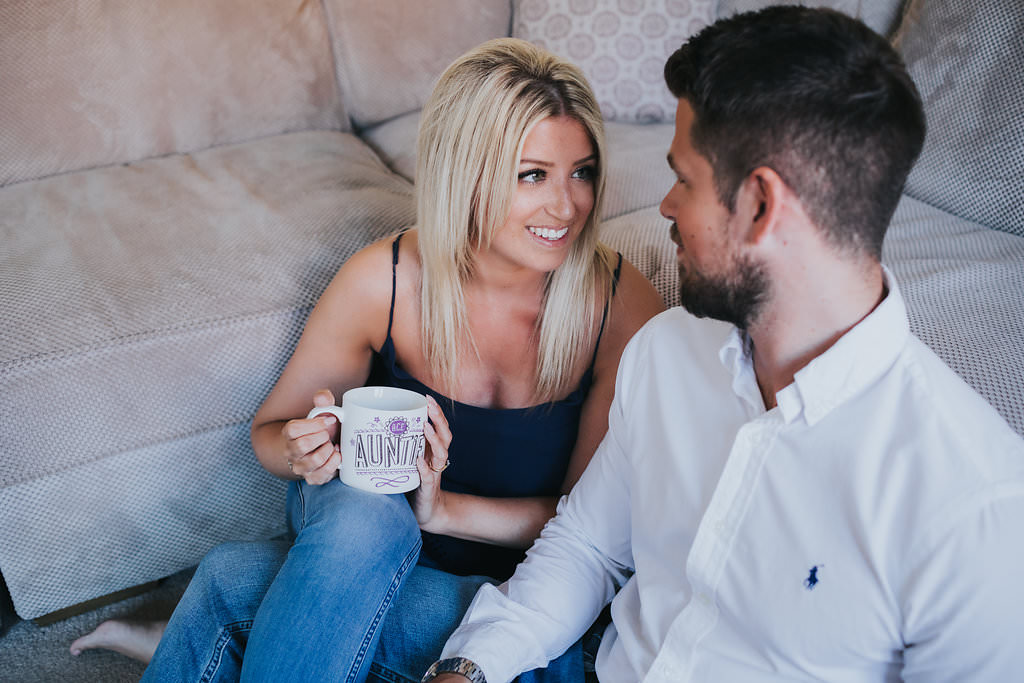 A bride to be is holding a mug while staring at her future husband.